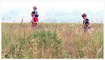 Familie mit Kind wnadert duch Wiese