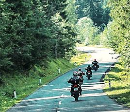 Motorradfahrer auf Landstraße durch Wald